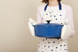 Anonymous woman holding a blue cast iron casserole dish
