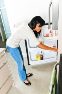 Young woman looking in refrigerator, stock pile