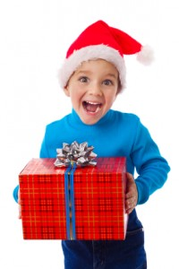 Laughing boy in Santa hat with red box
