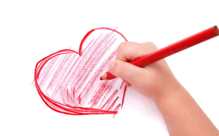 Childrens hand with pencil draws the heart