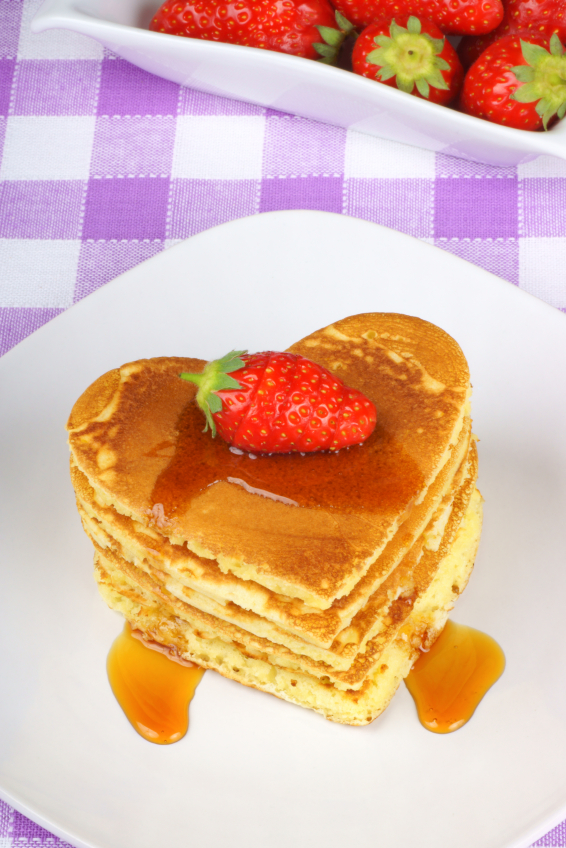 Stack of heart-shaped pancakes with syrup and strawberry