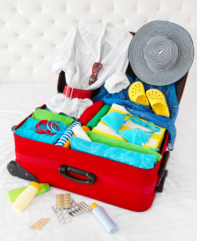 Travel suitcase packed for vacation with personal belongings. Co